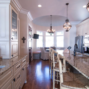 Large transitional eat-in kitchen in Charlotte with an undermount sink, raised-panel cabinets, beige cabinets, granite benchtops, beige splashback, matchstick tile splashback, stainless steel appliances, medium hardwood floors and with island.