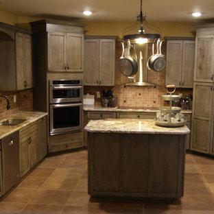 リトルロックの大きいエクレクティックスタイルのおしゃれなキッチン (シェーカースタイル扉のキャビネット、ヴィンテージ仕上げキャビネット、ラミネートカウンター、茶色いキッチンパネル、セラミックタイルのキッチンパネル、シルバーの調理設備の、アンダーカウンターシンク、セラミックタイルの床) の写真