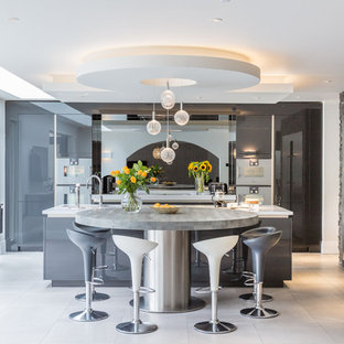 This is an example of a large contemporary eat-in kitchen in Manchester with a drop-in sink, grey cabinets, granite benchtops, metallic splashback, glass sheet splashback, stainless steel appliances, porcelain floors, multiple islands, grey floor and white benchtop.
