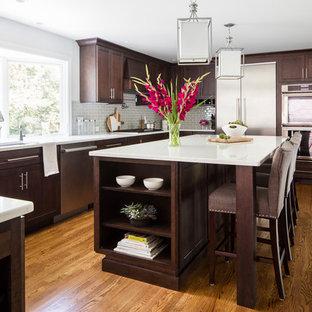 Klassisk inredning av ett kök, med en undermonterad diskho, skåp i shakerstil, bruna skåp, grått stänkskydd, stänkskydd i tunnelbanekakel, rostfria vitvaror, mellanmörkt trägolv, en köksö och brunt golv