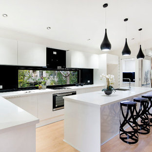 Photo of a contemporary l-shaped open plan kitchen in Brisbane with a submerged sink, flat-panel cabinets, white cabinets, window splashback, stainless steel appliances, plywood flooring and an island.