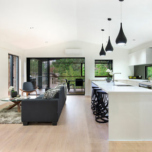 Design ideas for a contemporary galley open plan kitchen in Brisbane with an undermount sink, flat-panel cabinets, white cabinets, window splashback, black appliances, light hardwood floors, with island, beige floor and white benchtop.
