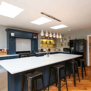Inspiration for a medium sized traditional l-shaped open plan kitchen in Other with shaker cabinets, blue cabinets, laminate countertops, white splashback, an island and white worktops.