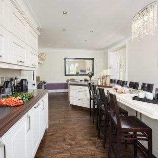 他の地域の大きいヴィクトリアン調のおしゃれなキッチン (アンダーカウンターシンク、シェーカースタイル扉のキャビネット、白いキャビネット、クオーツストーンカウンター、茶色いキッチンパネル、大理石の床、パネルと同色の調理設備、濃色無垢フローリング、茶色い床) の写真