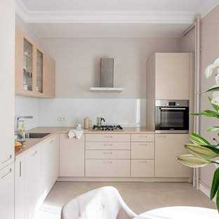This is an example of a small modern l-shaped eat-in kitchen in Other with an undermount sink, flat-panel cabinets, beige cabinets, quartz benchtops, white splashback, glass sheet splashback, stainless steel appliances, ceramic floors and no island.