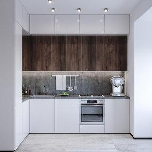 Kleine Moderne Wohnküche ohne Insel in L-Form mit Waschbecken, flächenbündigen Schrankfronten, weißen Schränken, Quarzit-Arbeitsplatte, Küchenrückwand in Grau, Rückwand aus Zementfliesen, Keramikboden, grauem Boden, Küchengeräten aus Edelstahl und grauer Arbeitsplatte in Frankfurt am Main