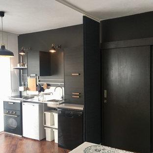 Esempio di una piccola cucina moderna con lavello a vasca singola, ante lisce, ante nere, top in acciaio inossidabile, paraspruzzi a specchio, elettrodomestici neri, pavimento in vinile e nessuna isola