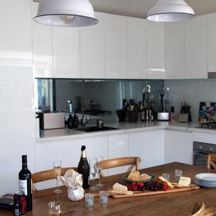 Idéer för ett exotiskt kök, med en undermonterad diskho, vita skåp, bänkskiva i kvarts, vitt stänkskydd, glaspanel som stänkskydd, rostfria vitvaror, betonggolv och en köksö