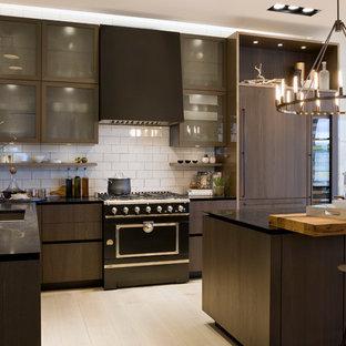 ワシントンD.C.のコンテンポラリースタイルのおしゃれなキッチン (フラットパネル扉のキャビネット、濃色木目調キャビネット、白いキッチンパネル、淡色無垢フローリング、アンダーカウンターシンク、サブウェイタイルのキッチンパネル、パネルと同色の調理設備) の写真