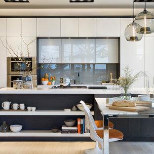 Cette photo montre une cuisine américaine linéaire tendance avec un placard à porte plane, des portes de placard blanches, un sol en bois clair, un îlot central, une crédence grise, un évier encastré, une crédence en feuille de verre et un électroménager encastrable.