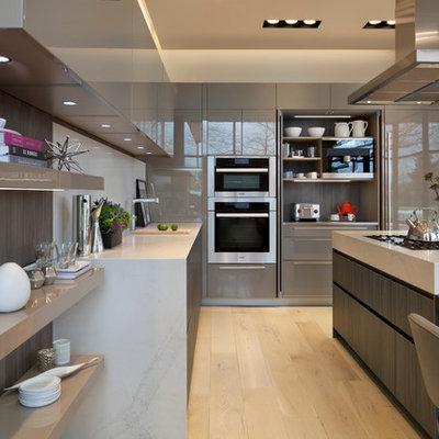 Trendy light wood floor eat-in kitchen photo in DC Metro with flat-panel cabinets, white backsplash, an island, an undermount sink, beige cabinets, stone slab backsplash and paneled appliances