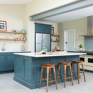 Photo of a medium sized traditional l-shaped kitchen/diner in London with shaker cabinets, blue cabinets, quartz worktops, an island, white worktops, blue splashback, stainless steel appliances, grey floors and exposed beams.