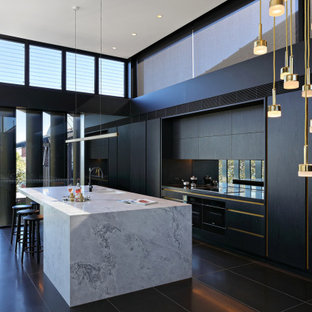 Design ideas for a large contemporary galley open plan kitchen in Sydney with a double-bowl sink, flat-panel cabinets, black cabinets, mirror splashback, panelled appliances, with island, black floor and grey benchtop.