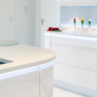 Mittelgroße Moderne Wohnküche in U-Form mit Doppelwaschbecken, flächenbündigen Schrankfronten, weißen Schränken, Arbeitsplatte aus Recyclingglas, Küchenrückwand in Weiß, Glasrückwand, Keramikboden, Kücheninsel und weißem Boden in Sonstige