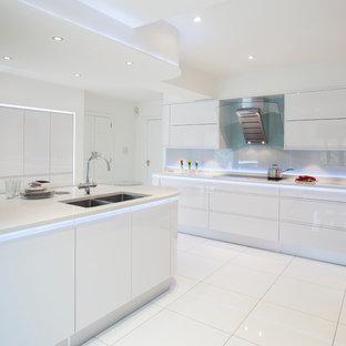 他の地域の中くらいのコンテンポラリースタイルのおしゃれなキッチン (ダブルシンク、フラットパネル扉のキャビネット、白いキャビネット、再生ガラスカウンター、白いキッチンパネル、ガラス板のキッチンパネル、セラミックタイルの床、白い床) の写真