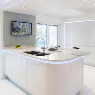 Inspiration for a medium sized contemporary u-shaped kitchen/diner in Other with a double-bowl sink, flat-panel cabinets, white cabinets, recycled glass countertops, white splashback, glass sheet splashback, ceramic flooring and an island.