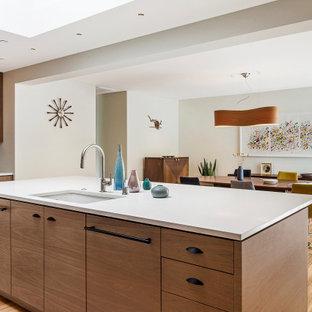 Стильный дизайн: кухня в стиле ретро с плоскими фасадами, фасадами цвета дерева среднего тона, гранитной столешницей, белым фартуком, фартуком из керамической плитки, островом и белой столешницей - последний тренд