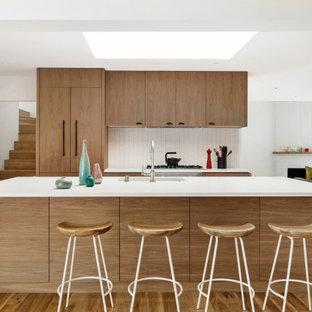Idéer för att renovera ett 50 tals vit vitt kök, med en integrerad diskho, släta luckor, skåp i mellenmörkt trä, granitbänkskiva, vitt stänkskydd, stänkskydd i keramik, integrerade vitvaror, ljust trägolv, en köksö och brunt golv