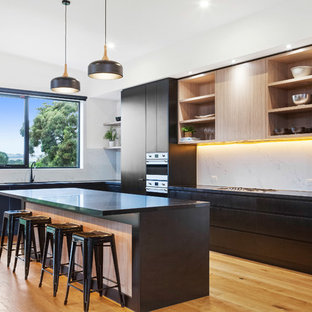 Design ideas for a contemporary l-shaped open plan kitchen in Melbourne with flat-panel cabinets, black cabinets, white splashback, black appliances, medium hardwood floors, with island and black benchtop.