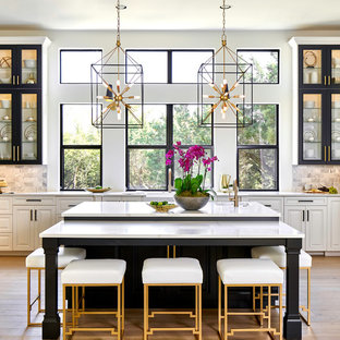Große Klassische Küche in U-Form mit Schrankfronten mit vertiefter Füllung, schwarzen Schränken, Quarzwerkstein-Arbeitsplatte, Rückwand aus Marmor, Küchengeräten aus Edelstahl, hellem Holzboden, Kücheninsel und weißer Arbeitsplatte in Austin