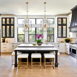 Imagen de cocina tradicional, grande, con puertas de armario negras, encimera de cuarzo compacto, electrodomésticos de acero inoxidable, suelo de madera clara, una isla, encimeras blancas, armarios tipo vitrina y salpicadero de vidrio