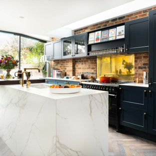 Inspiration for a traditional galley kitchen in London with a submerged sink, recessed-panel cabinets, black cabinets, red splashback, brick splashback, black appliances, dark hardwood flooring, an island, brown floors and white worktops.