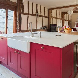 ケントの中サイズのカントリー風おしゃれなペニンシュラキッチン (エプロンフロントシンク、落し込みパネル扉のキャビネット、赤いキャビネット、トラバーチンの床) の写真