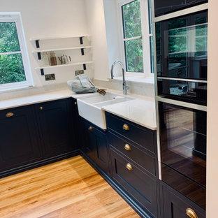 他の地域の広いコンテンポラリースタイルのおしゃれなキッチン (エプロンフロントシンク、シェーカースタイル扉のキャビネット、青いキャビネット、珪岩カウンター、黒い調理設備、無垢フローリング、青い床、白いキッチンカウンター) の写真