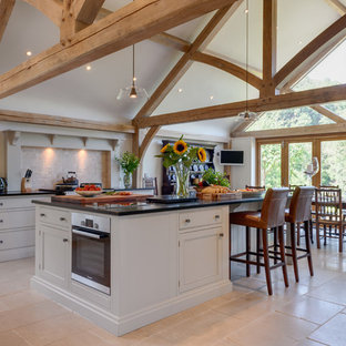 This is an example of a large rural single-wall kitchen in Other with recessed-panel cabinets, grey cabinets, beige splashback, stainless steel appliances, an island, beige floors and black worktops.