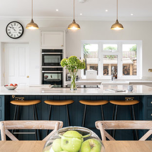 Design ideas for a large classic u-shaped kitchen/diner in Surrey with a belfast sink, beaded cabinets, white cabinets, quartz worktops, an island and white worktops.