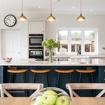 Stunning white kitchen with large dark blue island and marble worktops