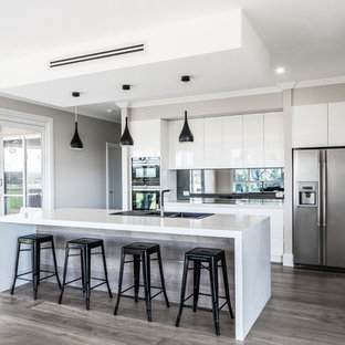 Large modern galley kitchen pantry in Sydney with a built-in sink, flat-panel cabinets, white cabinets, engineered stone countertops, black splashback, glass sheet splashback, stainless steel appliances, plywood flooring, an island and grey floors.