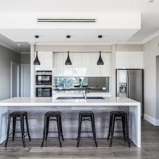 Ispirazione per una grande cucina minimalista con lavello da incasso, ante lisce, ante bianche, top in quarzo composito, paraspruzzi nero, paraspruzzi con lastra di vetro, elettrodomestici in acciaio inossidabile, pavimento in compensato, un'isola e pavimento grigio