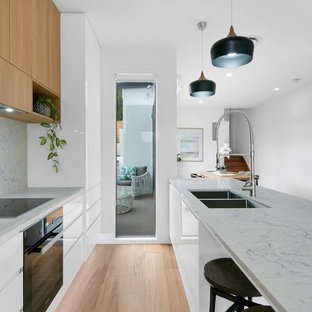 Photo of a contemporary galley separate kitchen in Brisbane with an undermount sink, flat-panel cabinets, medium wood cabinets, grey splashback, black appliances, light hardwood floors, with island, beige floor and grey benchtop.