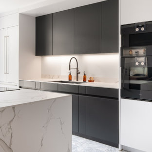 Inspiration for a mid-sized modern eat-in kitchen in Gloucestershire with flat-panel cabinets, grey cabinets, solid surface benchtops, black appliances, marble floors, with island and white benchtop.