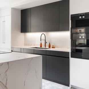 Immagine di una cucina moderna di medie dimensioni con ante lisce, top in superficie solida, elettrodomestici neri, pavimento in marmo, top bianco, lavello sottopiano, ante nere e pavimento grigio