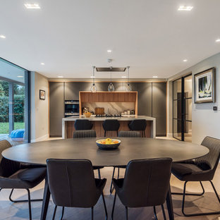 Design ideas for a contemporary single-wall open plan kitchen in Hertfordshire with light hardwood flooring, beige floors, flat-panel cabinets, grey cabinets, white splashback, an island and white worktops.