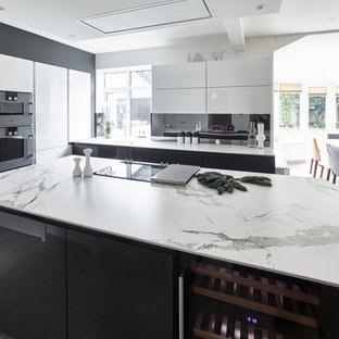 This is an example of a large contemporary l-shaped open plan kitchen in Other with flat-panel cabinets, quartz benchtops, grey splashback, mirror splashback, with island, white cabinets, coloured appliances, porcelain floors, beige floor and white benchtop.
