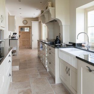 Design ideas for a small classic galley kitchen in Kent with a built-in sink, white cabinets, granite worktops, integrated appliances and porcelain flooring.