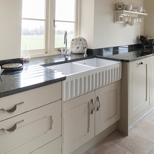 Small traditional galley kitchen in Kent with a belfast sink, white cabinets, granite worktops and porcelain flooring.