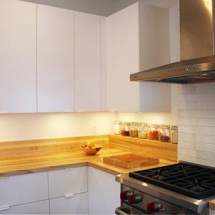 ニューヨークの中くらいのモダンスタイルのおしゃれなキッチン (アンダーカウンターシンク、フラットパネル扉のキャビネット、白いキャビネット、木材カウンター、シルバーの調理設備、クッションフロア) の写真