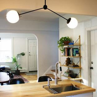 ニューヨークの中サイズのモダンスタイルのおしゃれなキッチン (アンダーカウンターシンク、フラットパネル扉のキャビネット、白いキャビネット、木材カウンター、シルバーの調理設備の、クッションフロア) の写真