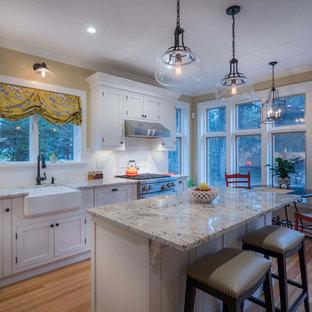 Mittelgroße Wohnküche in L-Form mit Landhausspüle, Schrankfronten mit vertiefter Füllung, weißen Schränken, Granit-Arbeitsplatte, Küchenrückwand in Weiß, Küchengeräten aus Edelstahl, Sperrholzboden und Kücheninsel in New York