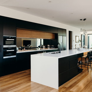 Inspiration for a contemporary open plan kitchen in Newcastle - Maitland with a double-bowl sink, flat-panel cabinets, black cabinets, mirror splashback, black appliances, with island, white benchtop and light hardwood floors.