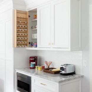 Cette photo montre une cuisine chic avec un plan de travail en marbre, une crédence blanche, un électroménager en acier inoxydable, un sol en bois foncé, un sol marron, un placard avec porte à panneau encastré, des portes de placard blanches, une crédence en carrelage métro et un plan de travail gris.