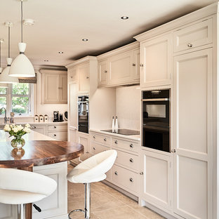Design ideas for a medium sized traditional kitchen in Other with recessed-panel cabinets, white cabinets, quartz worktops, an island, white worktops, white splashback, mosaic tiled splashback, black appliances and brown floors.