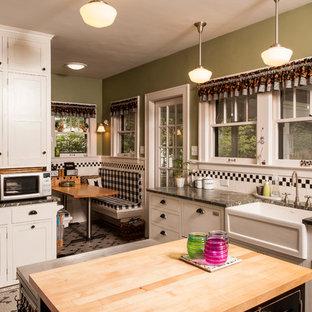 デトロイトの中サイズのトラディショナルスタイルのおしゃれなキッチン (エプロンフロントシンク、シェーカースタイル扉のキャビネット、白いキャビネット、御影石カウンター、黒いキッチンパネル、サブウェイタイルのキッチンパネル、黒い調理設備、セラミックタイルの床、緑のキッチンカウンター) の写真