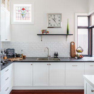 This is an example of a transitional l-shaped kitchen in Perth with shaker cabinets, white cabinets, quartz benchtops, white splashback, subway tile splashback, stainless steel appliances, with island, a double-bowl sink, medium hardwood floors, brown floor and black benchtop.