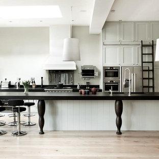 Zweizeilige, Geräumige Klassische Küche mit Vorratsschrank, Einbauwaschbecken, Schrankfronten im Shaker-Stil, grünen Schränken, Arbeitsplatte aus Holz, Küchenrückwand in Schwarz, Rückwand aus Stein, Küchengeräten aus Edelstahl, braunem Holzboden, Kücheninsel, braunem Boden und schwarzer Arbeitsplatte in London