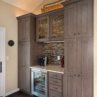 デンバーの大きいカントリー風おしゃれなキッチン (エプロンフロントシンク、シェーカースタイル扉のキャビネット、濃色木目調キャビネット、クオーツストーンカウンター、茶色いキッチンパネル、パネルと同色の調理設備、無垢フローリング、茶色い床、白いキッチンカウンター) の写真